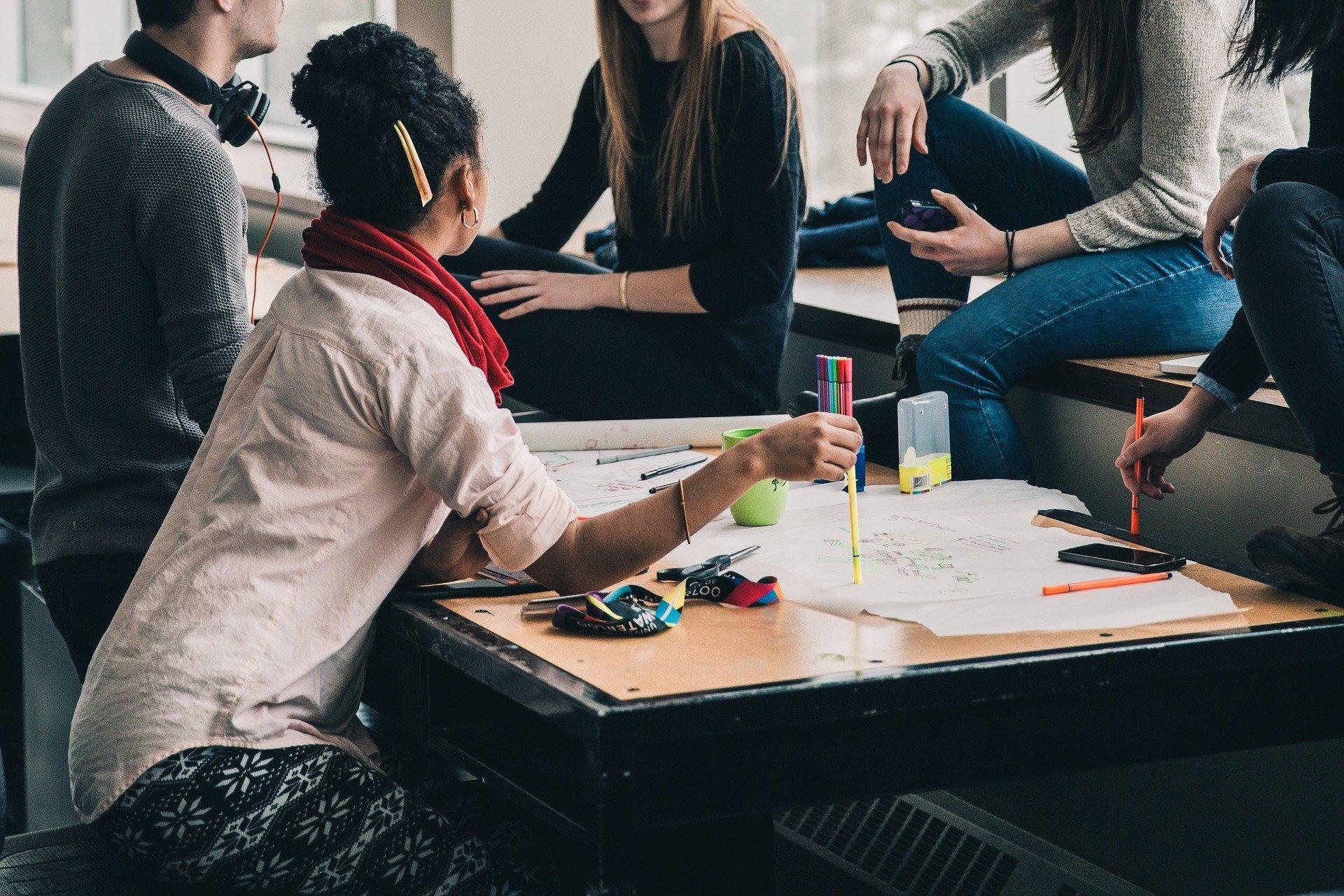 Studierende sitzen um einen Tisch herum und diskutieren
