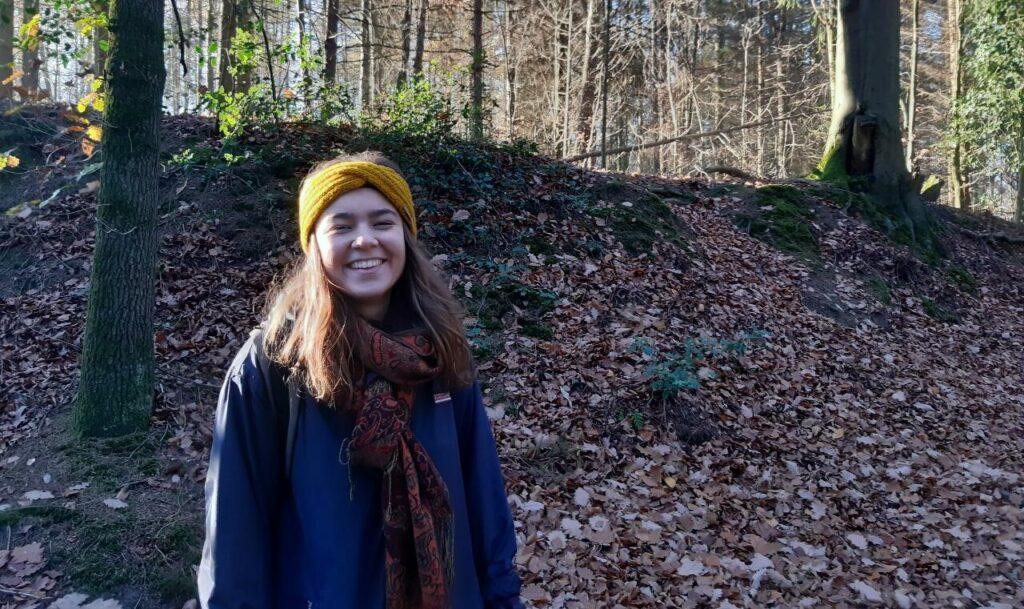 Annika hat eine Hörbeeinträchtigung. Sie steht in einem Wald und lächelt in die Kamera.
