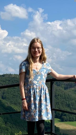 Studentin Marie steht an einem Zaun einer Aussichtsplattform