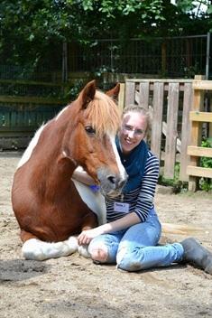 Studentin Marina hat eine chronische Erkrankung.Sie kniet neben einem liegenden Pferd.