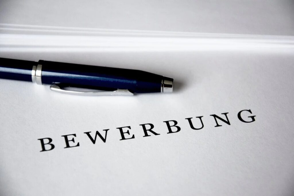 """Ein Blatt, auf dem """"Bewerbung"""" steht. Außerdem liegt ein blauer Kugelschreiber auf dem Blatt."""