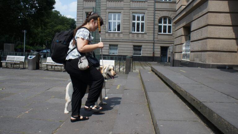 Die blinde Studentin Carina und ihr Blindenführhund Pitou gehen eine Treppe der TH Köln hinauf