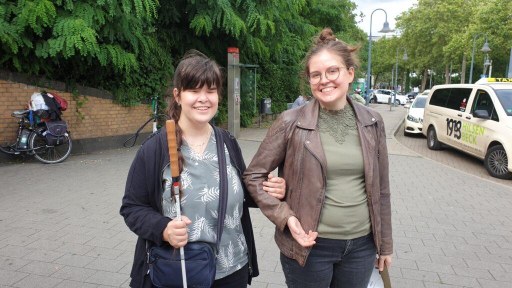 Studienassistenz Hella steht neben ihrer Arbeitgeberin Carina, Carina hat sich bei Hella eingeharkt