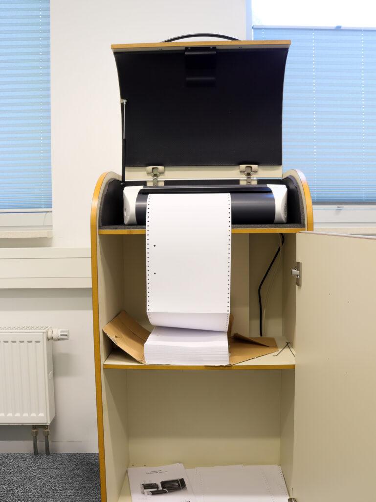 Ein Brailleschriftdrucker für Blinde steht in einem Schallschluckschrank.