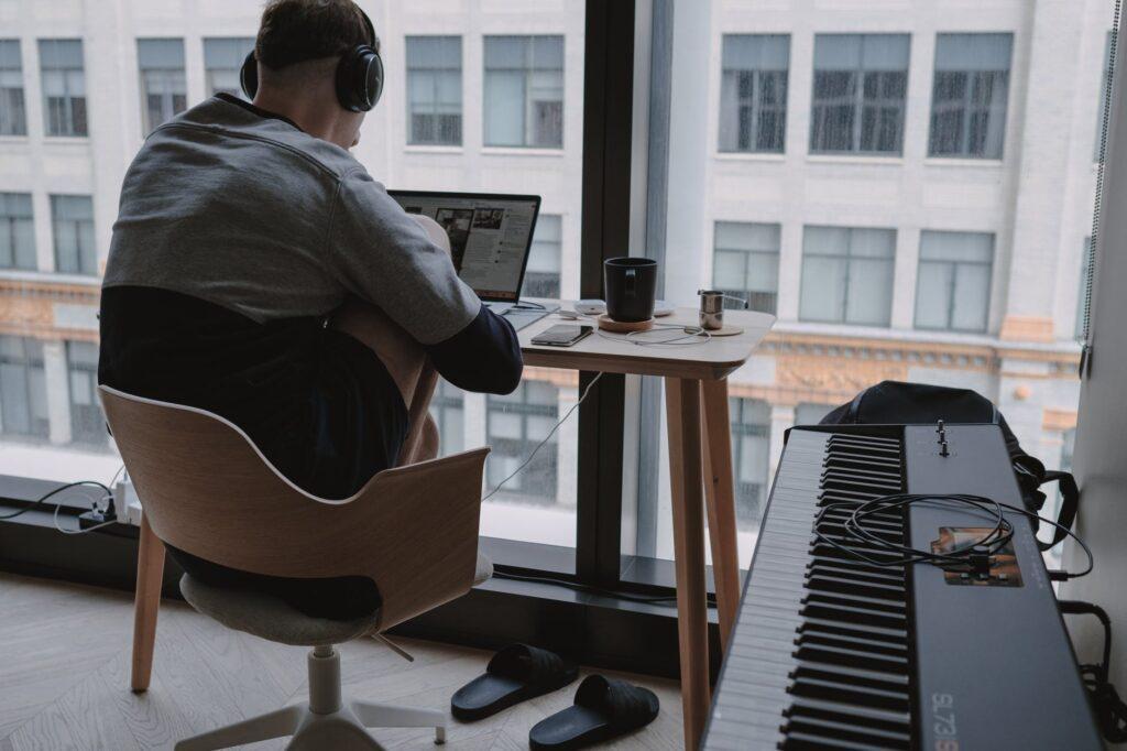 Ein Mann von hinten mit Kopfhörern vor einem Laptop. Neben ihm steht ein Keyboard.
