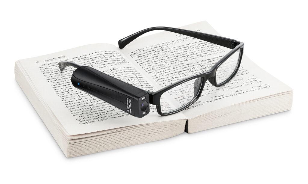 winziges Hilfsmittel: Eine OrCam an einer Brille auf einem Buch