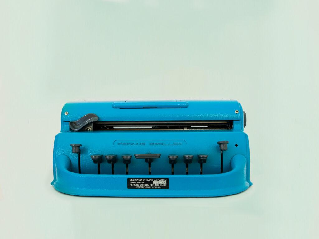 Eine Blindenschriftschreibmaschine vor hellblauem Hintergrund