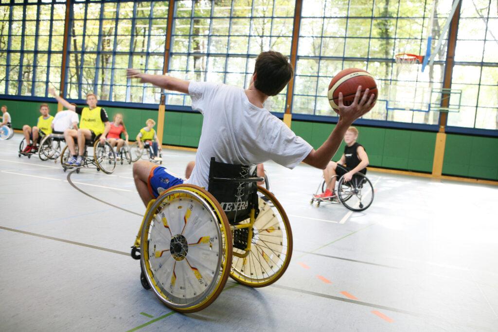 Mehrere Menschen spielen Rollstuhlbasketball in der Turnhalle der Deutschen Sporthochschule Köln