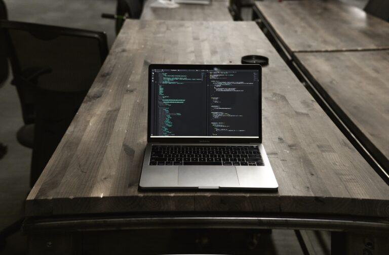 Ein Laptop mit Programmiercode auf einem Schreibtisch