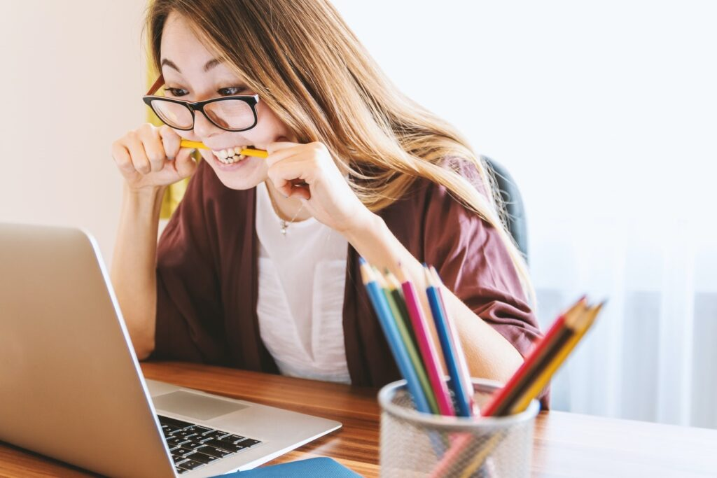 Frau beißt in Bleistift während sie auf ihren Laptop schaut