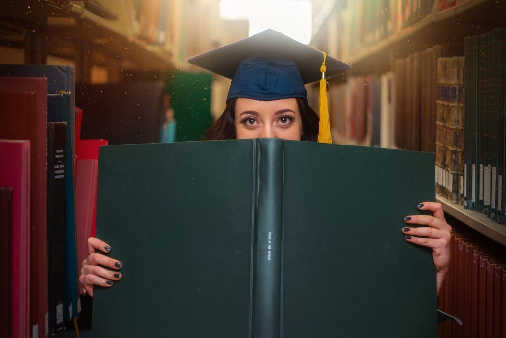 Absolventin mit Doktorhut, die ihr halbes Gesicht hinter einem Buch versteckt