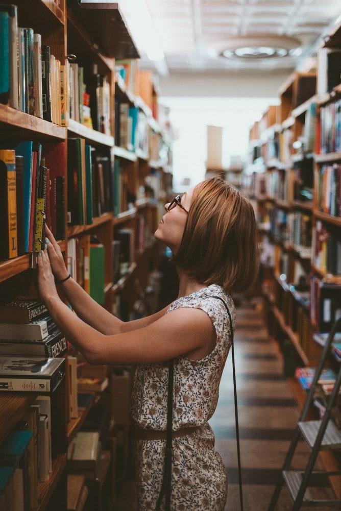 Eine Frau sucht nach einem Buch in einer Bibliothek