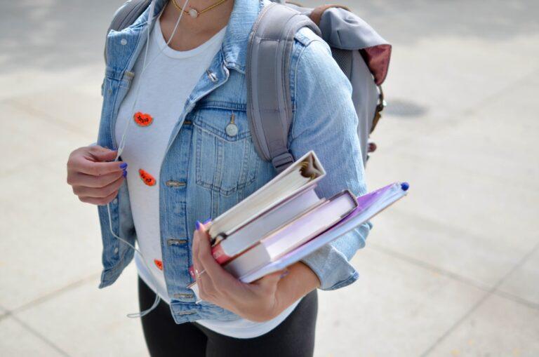 eine weibliche Person mit Büchern unterm Arm
