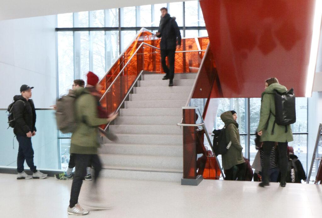 Mehrere Studierende mit und ohne Beeinträchtigung gehen eine Treppe in der deutschen Sporthochschule Köln hinauf oder herunter