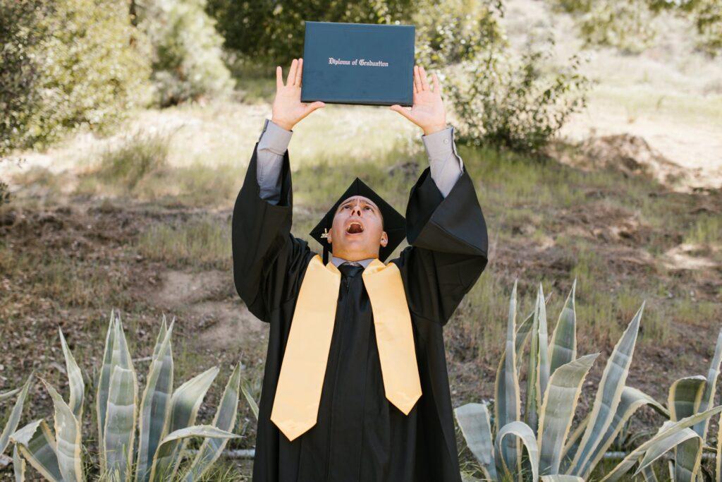 "Student mit Doktorhut hält sein ""Diploma of Graduation"" hoch"